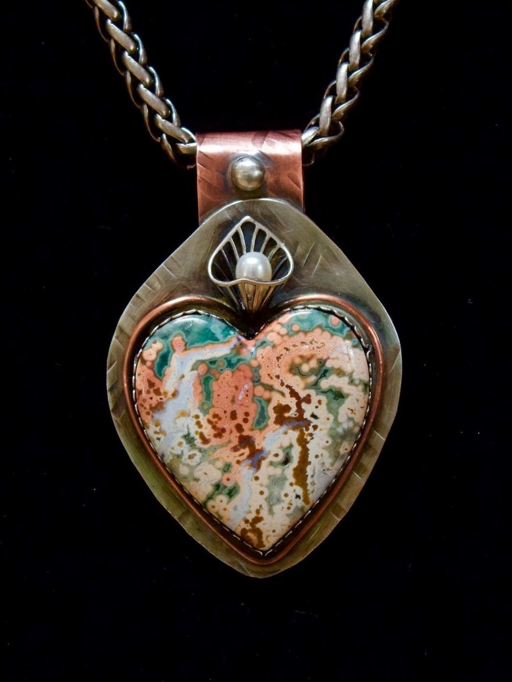 "- I do love hearts! I can only express the feeling this amazing stone has by giving it the title ""What Lies Within The Heart"". Lapidarian Russ Kaniuth shaped this old stock ocean jasper stone and I set it in sterling silver with a pearl accent. It struck the heart of a collector in New Mexico and lives there happily ever after."
