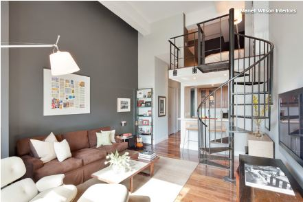 In This Double Height Living Room The Cool Character Of Charcoal Accent Wall Tones Down Warm Honey Wood And Brown Sofa