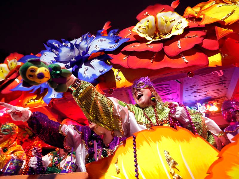 Float riders toss trinkets as the Krewe of Orpheus rolls in New Orleans in 2018. (AP Photo/Gerald Herbert)