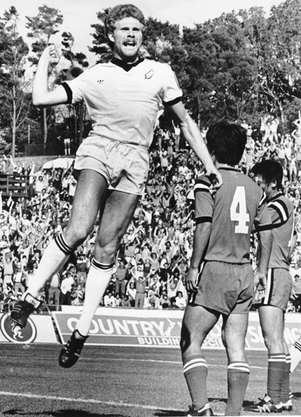 New Zealand defender Ricki Herbert raising his arm in triumph after scoring New Zealand's goal in a World Cup qualification match in 1981.