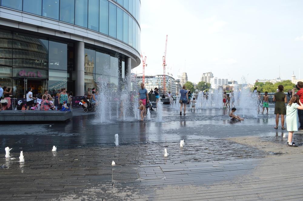 """Espaço público. Crianças brincando com água na frente de restaurantes """"finos""""."""