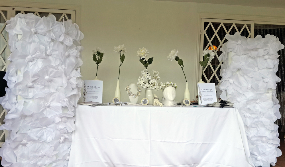 Shaunelle. Table display design by Shaunelle Ramesar featuring side columns embellished with handmade flowers.