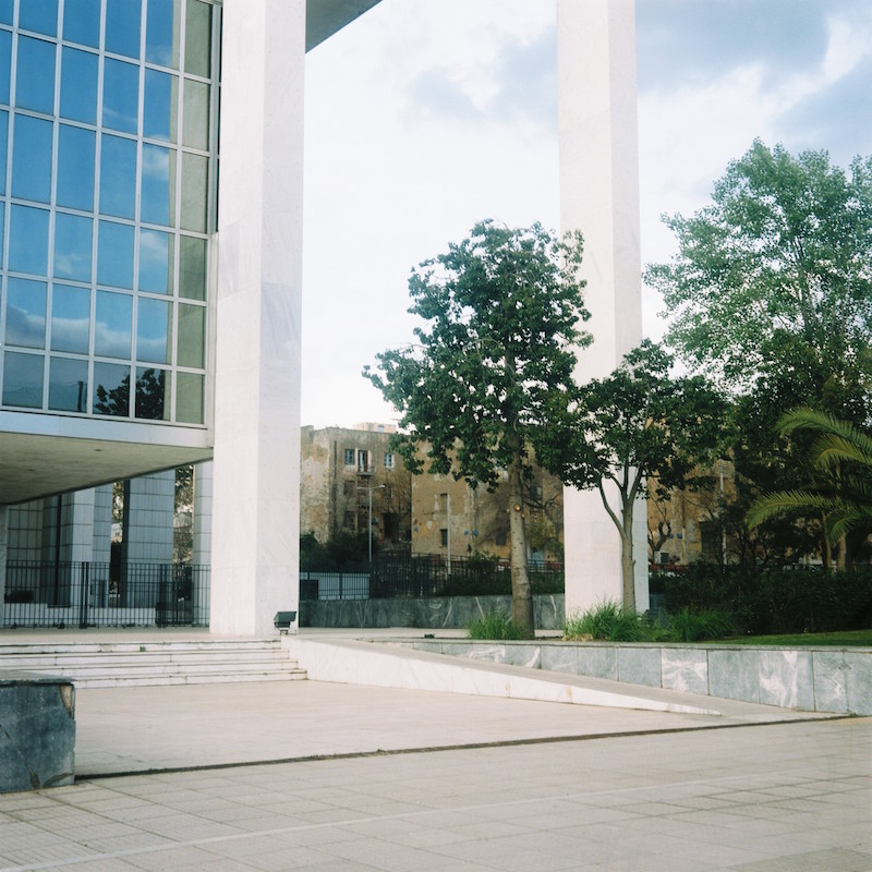 The Prosfygika estate can be seen through the modern archway of the Courts of Justice next door.