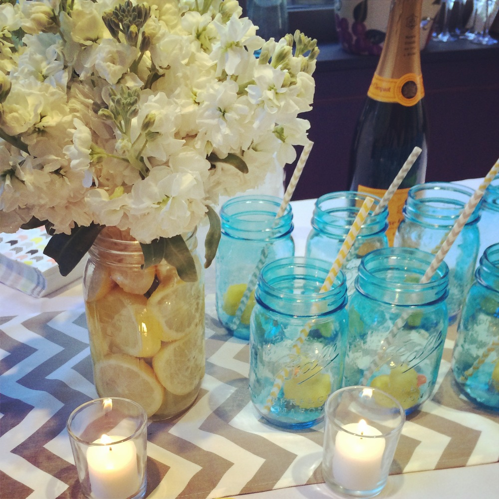 Arrangements of white stock flowers and mason jars with striped straws and rubber ducks adorned the bar