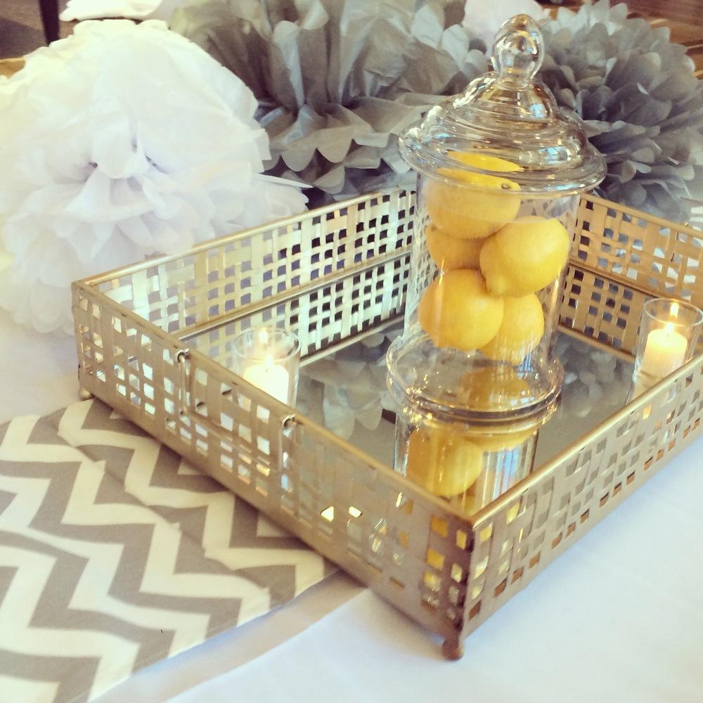 Mirrored trays with lemon-filled glass jars and votive candles