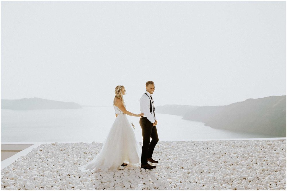 A bride and groom having their first look on a rooftop in Santorini