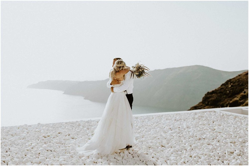 A bride and groom hugging in Santorini