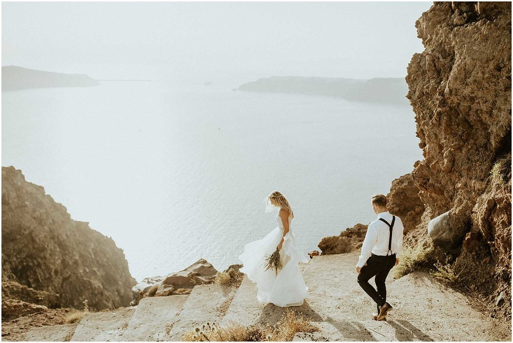 A bride and groom hike to their wedding in Santorini