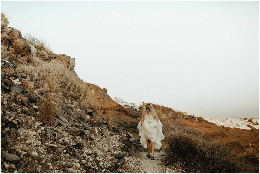 A bride hiking at Skaros rock in Santorini