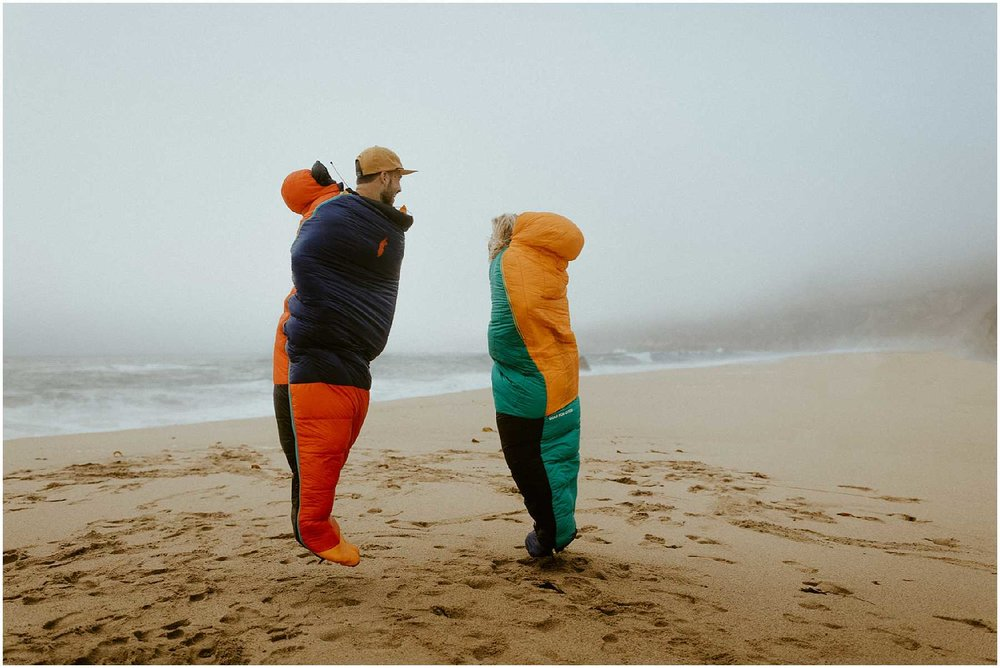 An adventurous couple in their Cotopaxi sleeping bags in Big Sur