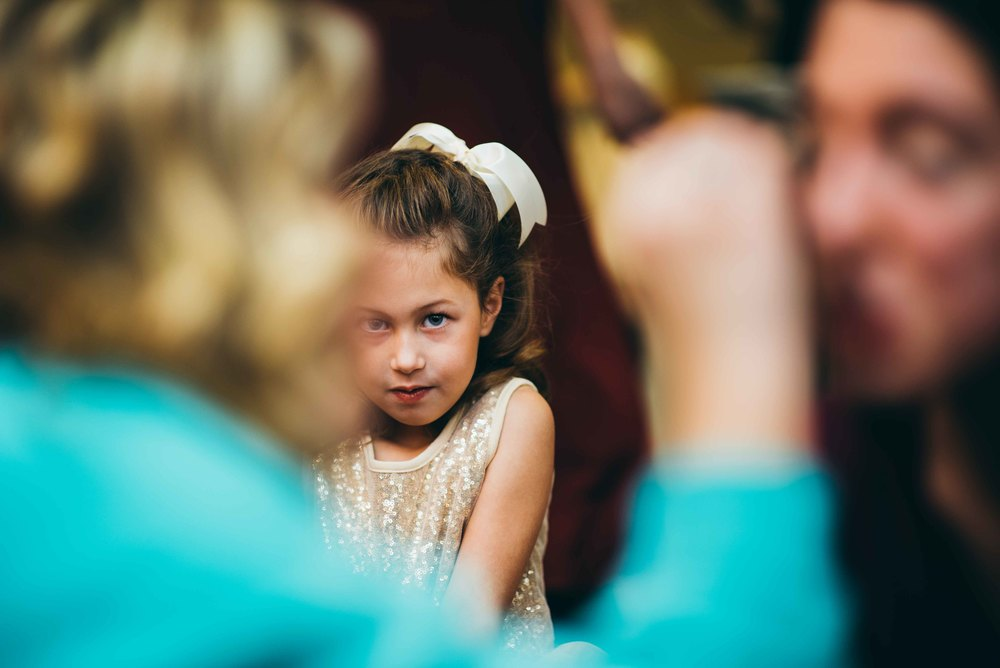A flower girl looking on as the bride has her makeup done.