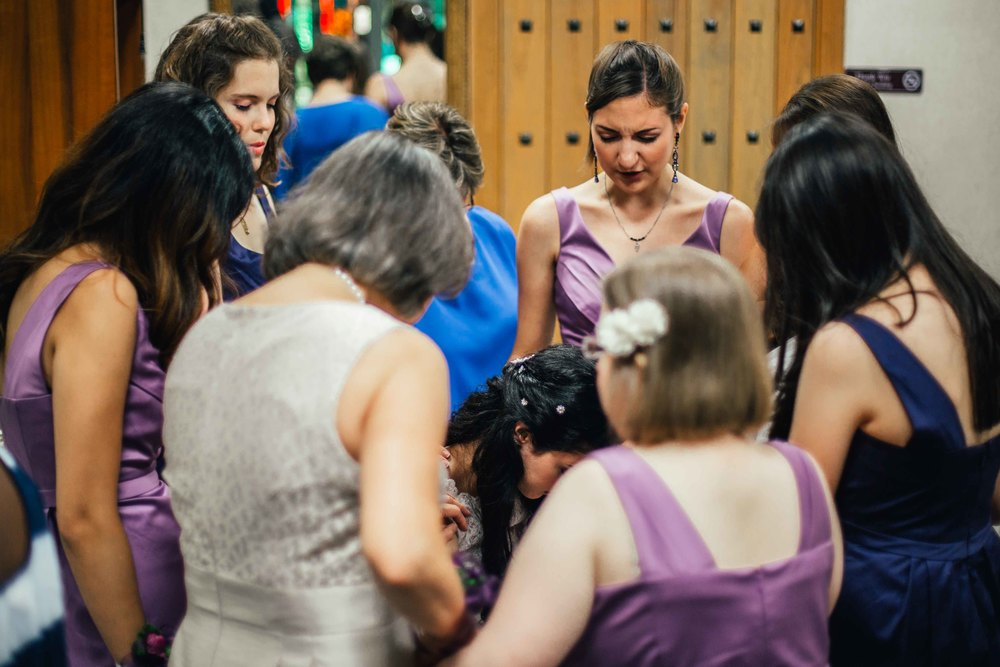 The Bridesmaids praying around the Bride. Its important to capture these moments, while remaining unobtrusive.