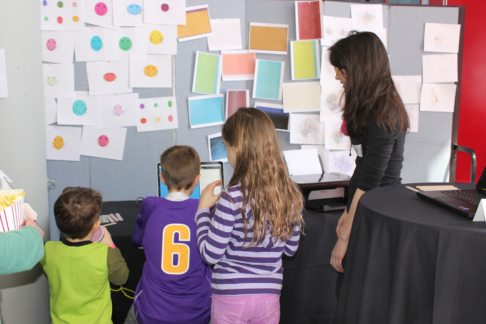 Caroline Record, pictured right, is seen interacting with visitors during her art and code tutorial.  Images created by students (with code!) are hanging on the wall behind the coding stations.
