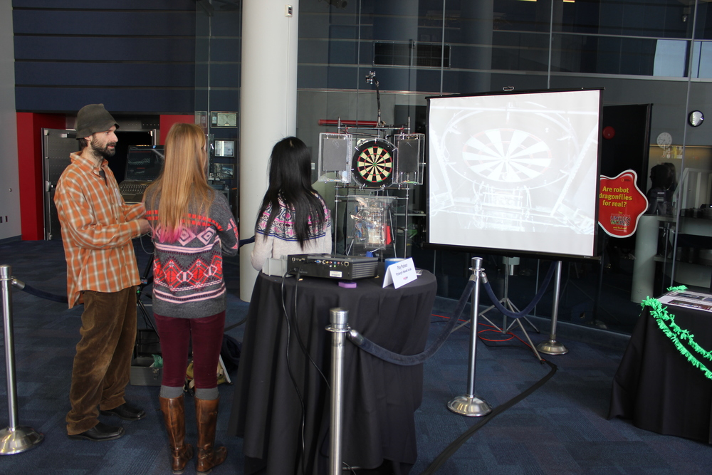 Adam Schreckhise, of Pittsburgh PLAY Parlour, explains the mechanics of his self engineered, nomadic arcade game.  The image and sound output from the dartboard changes depending on how fast you throw the dart and how close to the target the dart lands.