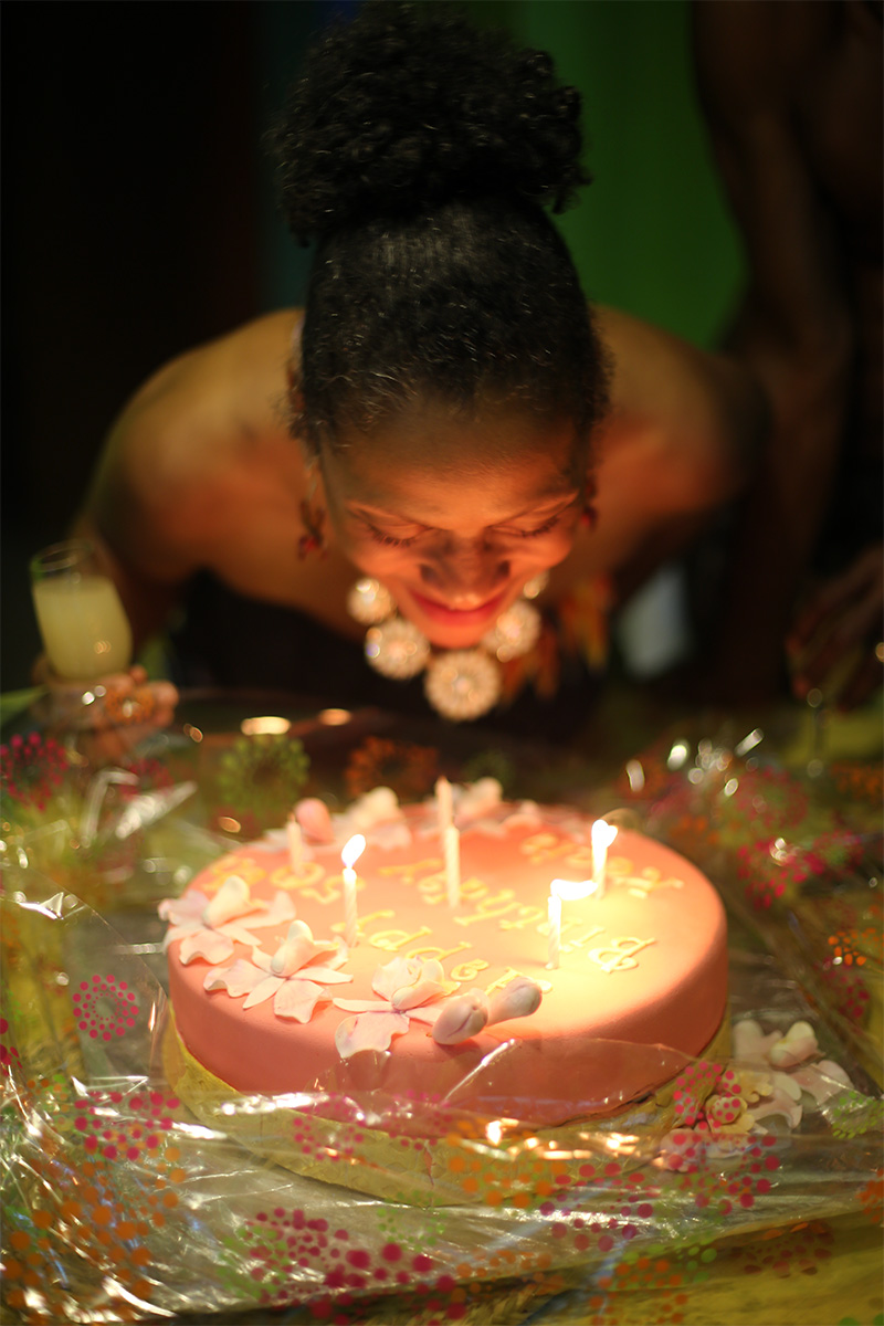 Blowing out the candles on my birthday cake with a glass of sea moss in my hand.
