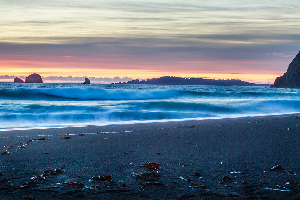 Waves crashing into the beach with the lights from Port Orford in the distance. Humbug Mountain, Oregon