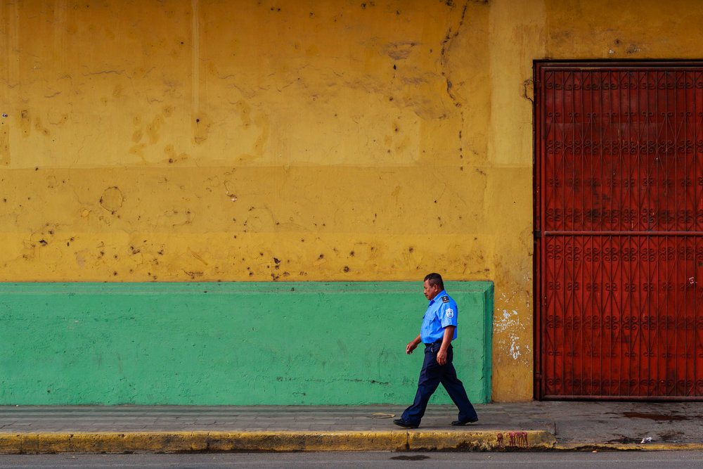 Security guard walking along the colorful streets of Granada, Nicaragua.