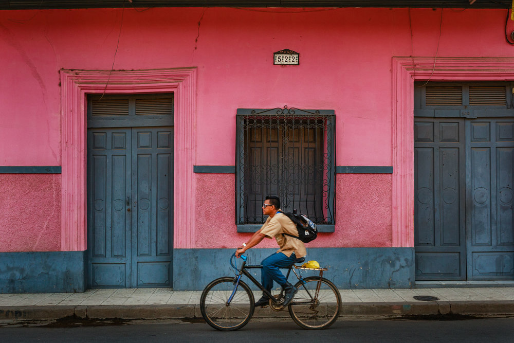 Man riding his bike to work on a warm morning commute on the colorful streets of Granda, Nicaragua.