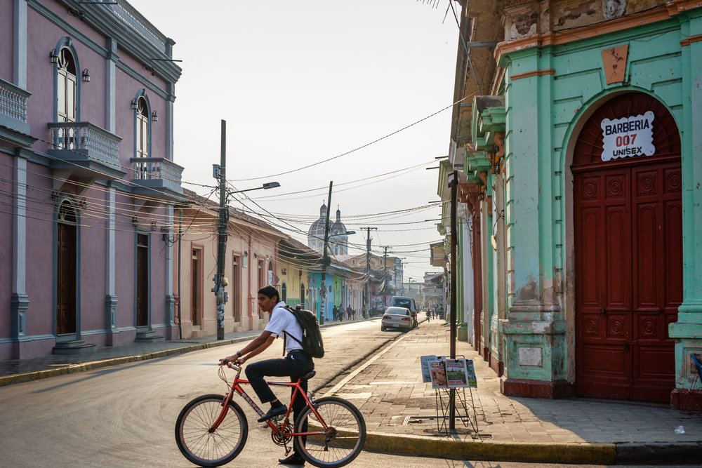 Young man riding his bike to work on a warm morning commute on the colorful streets of Granda, Nicaragua.