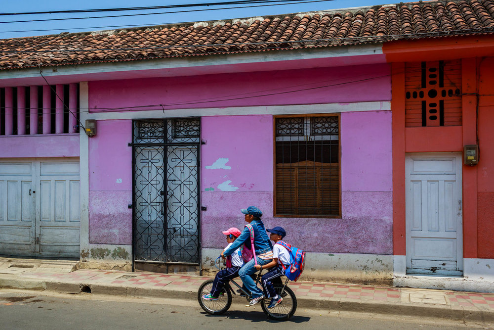 Mom riding her kids to school down the colorful streets of Granada, Nicaragua.