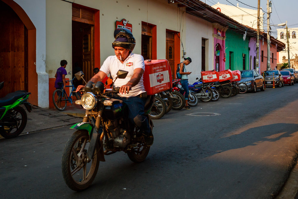 Delivery driver smoking a cigarette while driving his motorcycle on the streets of Granada, Nicaragua.