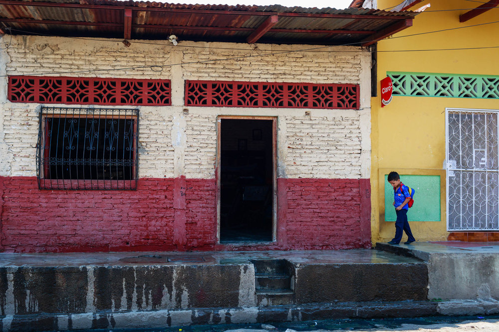 Young boy walking to school down a street covered in a rainbow of colors in Granada, Nicaragua.
