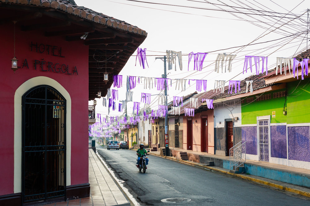 Motorcycle riding down a colorful street lined with small flags in Granada, Nicaragua.