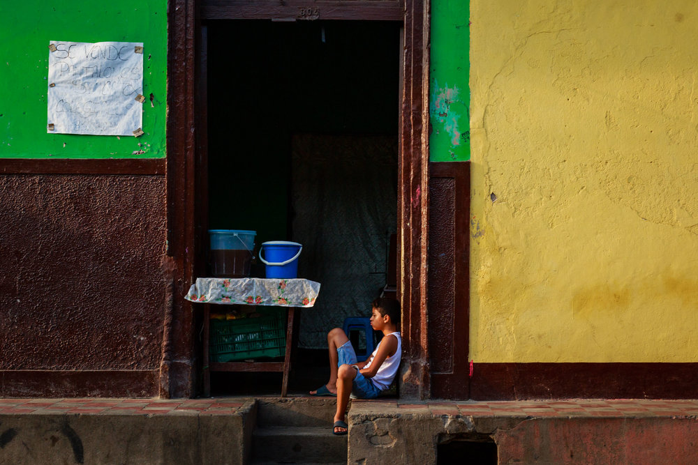 Young boy sitting in the doorway on a hot morning along the colorful streets of Granada, Nicaragua