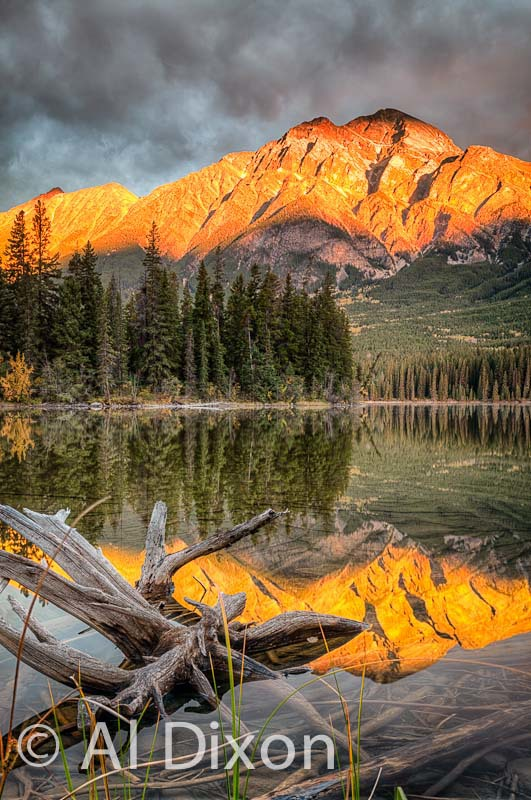 Thin ray of morning sun lights the face of Pyramid Mountain in Jasper National Park.