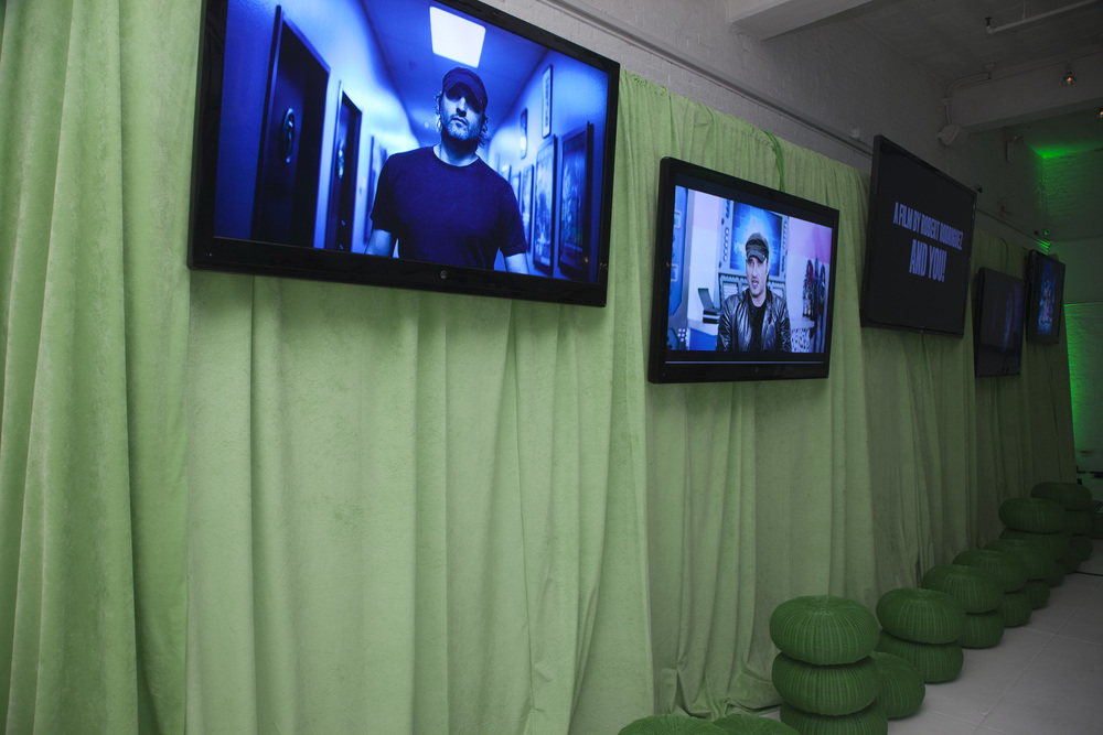 Gallery of monitors showcasing fan submissions set on a green screen-inspired backdrop