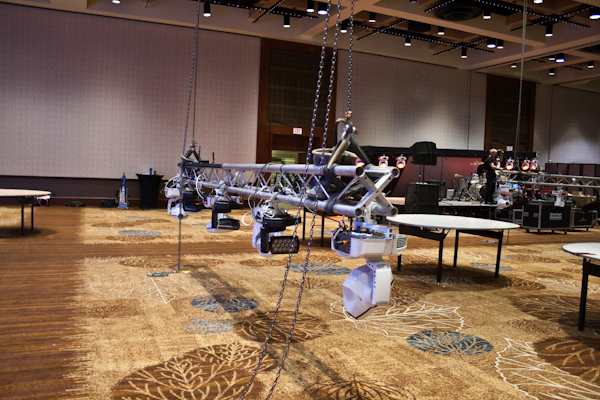 Transforming an event space — trusses being rigged with audio and lighting equipment