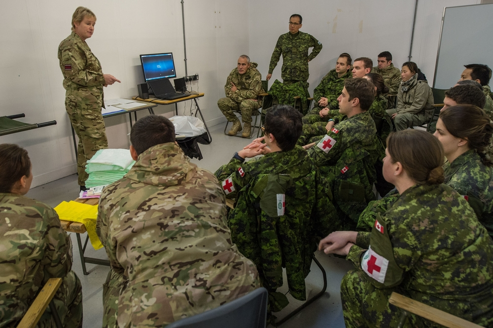 Canadian and British Armed Forces medical personnel engage in a debriefing during Operation SIRONA pre-deployment training at the Army Medical Services Training Centre in Strensall, UK in 2014.