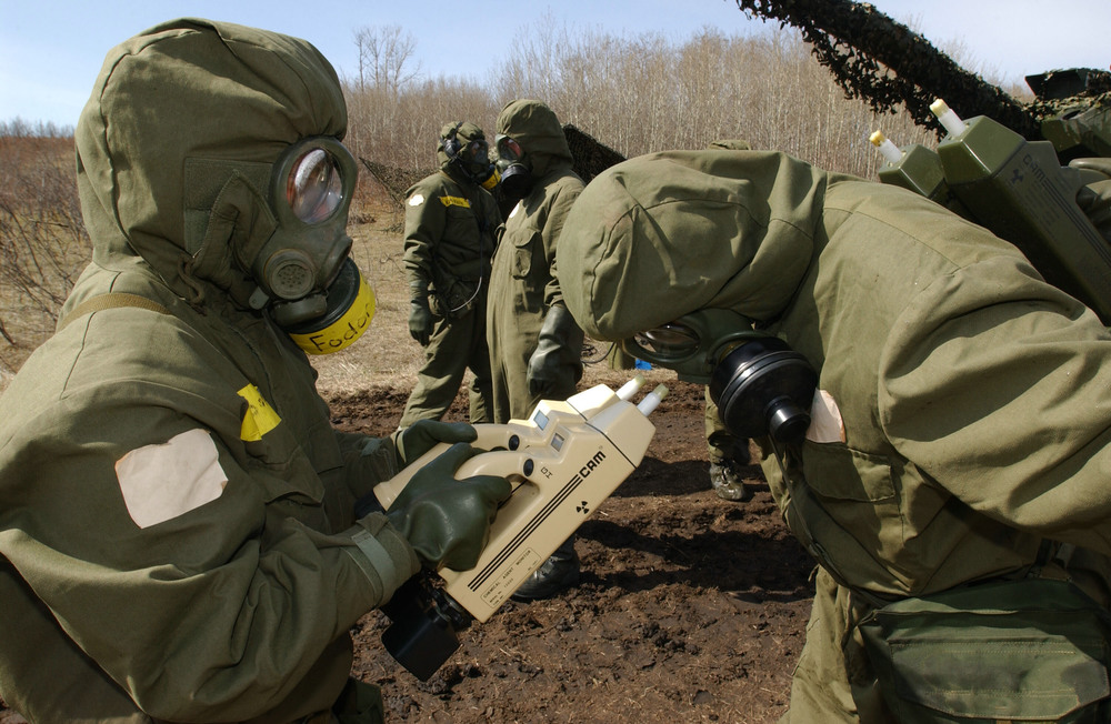 Private Jennifer Fodor, a member of 2 General Support Battalion from Petawawa, Ontario, checks Warrant Officer Benson for chemical contamination with two chemical agent monitors (CAM) during a decontamination operation. (Combat Camera)