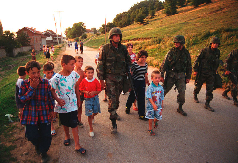 A U.S. Marine Corps sergeant accompanies local children down a street in Zegra, Kosovo at the time of the NATO entry into Kosovo in 1999. More than 15 years on, the mass exodus of Albanian Kosovars that occurred during the Serbia-Kosovo conflict is being repeated in the present day - not due to war, but due to the harsh economic conditions in the quasi-state of Kosovo. (U.S. Department of Defense)