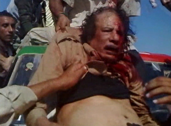 Moammar Gadhafi being dragged through the streets, where he was eventually beaten and shot to death. (Wikimedia photo).