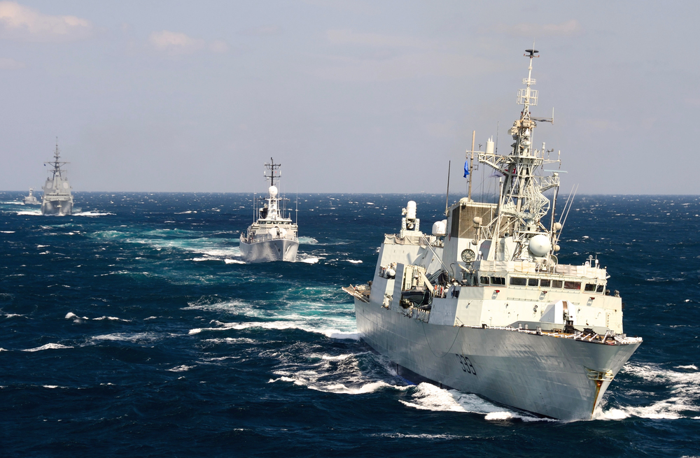 HMCS Toronto, a Halifax-class frigate, leads a fleet of North Atlantic Treaty Organization (NATO) ships through the Black Sea while conducting a training exercise during Operation REASSURANCE in September 2014. Along with the Iroquois-class destroyer ships, the frigates will be replaced under the Canadian Surface Combatant (CSC) program, which will be one of the first procurement projects to be affected by the government's new Defence Procurement Strategy (DPS). (Sgt Matthew McGregor, Combat Camera)