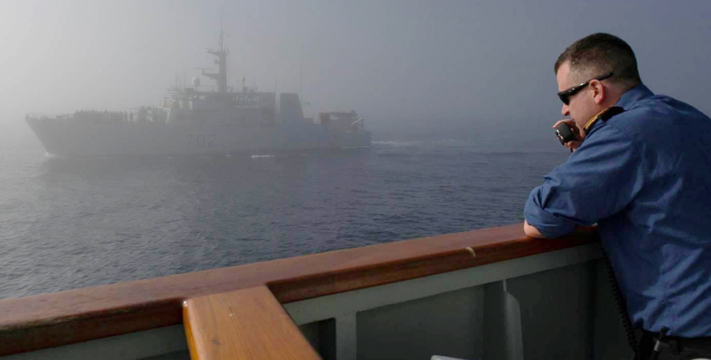 LCdr Christopher Rochon, speaking on his radio to the commanding officer of HMCS Nanaimo (seen through the fog in the background), during a seamanship evaluation (you can see Nanaimo's ship's company formed up on the forecastle) off the coast of northern California en route to the OP CARIBBE area of operations (AOO) on February 17, 2015. (Cpl. Blaine Sewell, DND)