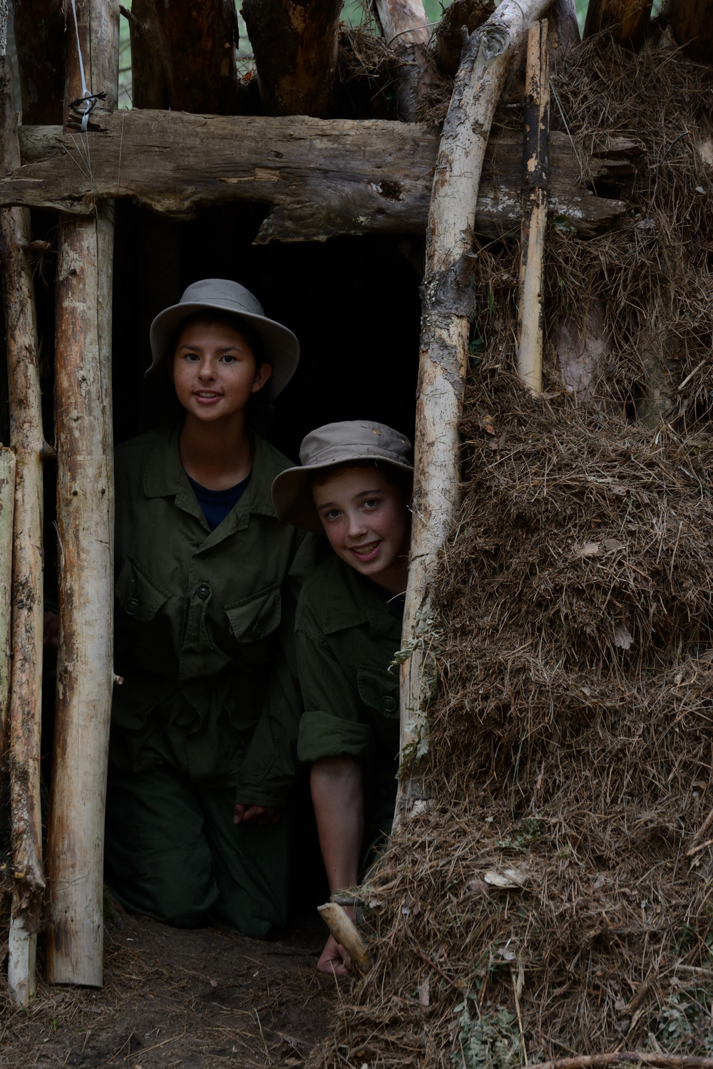 Jacob Partello and Harmony Buswa demonstrate just how roomy a wilderness shelter made of logs and pine-needs can be. Air Cadets in the basic Survival Course are trained to choose campsites, start and maintain fires and build shelters, before going on a wilderness trek to prove their survival capabilities. (Sgt Kev Parle, DND)