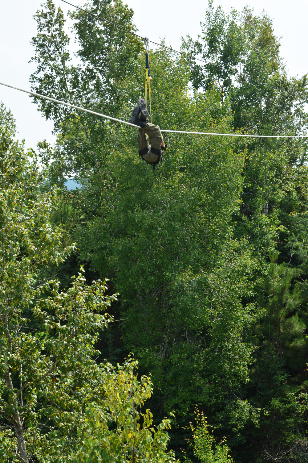 Army Cadet Kevin Mycroft inches his way across a gorge on the single-strand rope bridge as part of the General Training (GT) course at CFB Borden. (Sgt Kevin Parle, DND)