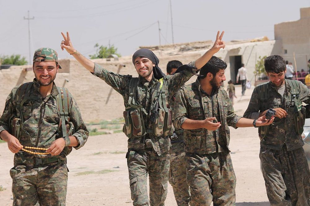 Members of the YPG (People's Protection Units) Kurdish militia, who have recently been joined by Canadian volunteers eager to fight against ISIS. Under the Conservative government's planned travel plan, Canadian nationals seeking to fight as civilian volunteers may find themselves running afoul of the law, especially given the recent hostilities between Turkey - a NATO ally - and the Kurdish revolutionaries, who include in their numbers the PKK, a designated terrorist organization. (Wikipedia)
