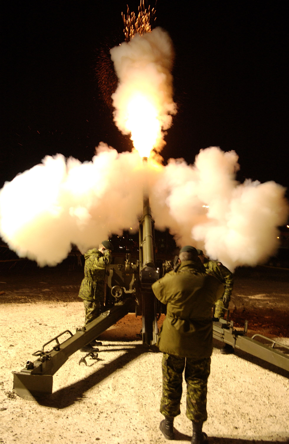 Gunners fire a C3 Howser during a nighttime exercise. This is a close support, field artillery weapon that is mobile, general purpose, light towed, and has the capability to fire extended range munitions up to 18 kilometres. The C3 is manually operated, single-loaded and air-cooled. The C3 is structurally similar to the C1 Howitzer, but is distinguished by its longer 33-calibre barrel and muzzle brake. The gun can fire all standard NATO 105mm Howitzer ammunition. (DND)