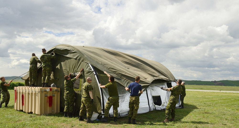 Members of Canadian Air Task Force put up tents in Câmpia Turzii, Romania, during NATO reassurance measures on May 10, 2014. The old-style canvas tents require a significant number of people and time to set up. New technology permits companies like HDT Global to develop easy-to-assemble, lightweight, durable deployable shelters that are easier and faster to set up yet can withstand harsh environments and be unsupplied for longer periods of time. (DND)