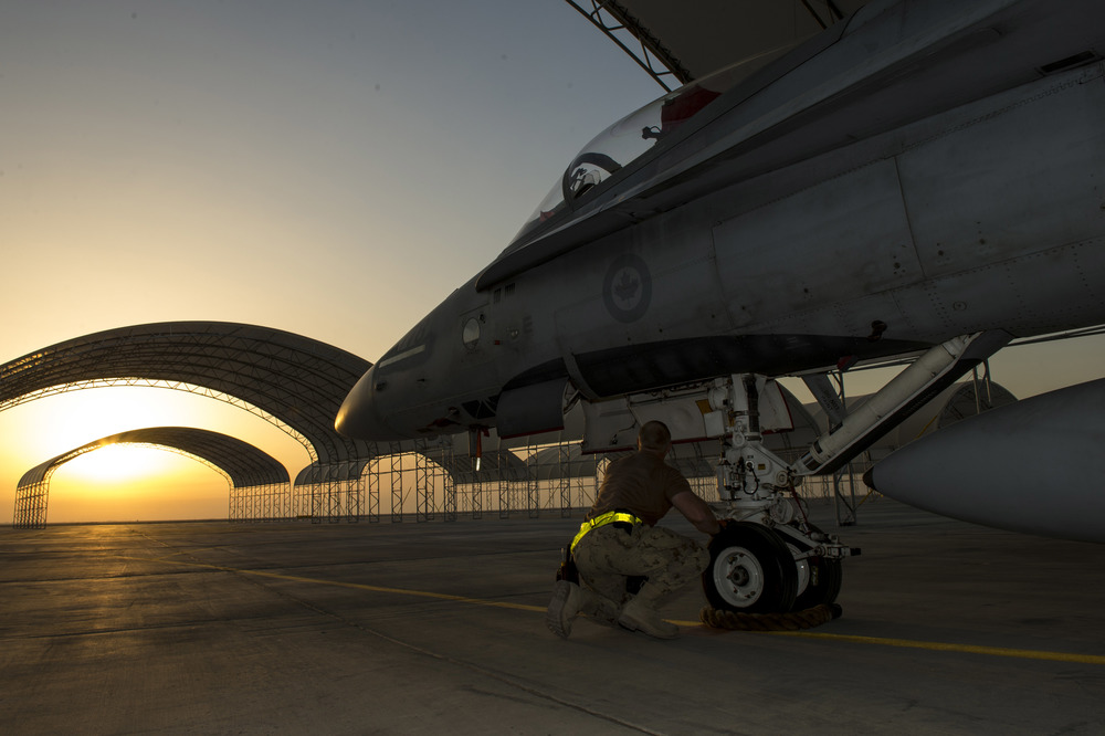 An aircraft technician from Air Task Force – Iraq inspects the nose landing gear of a CF-188 Hornet aircraft at the Camp Patrice Vincent flight line, in Kuwait during Operation IMPACT on December 11, 2015. (combat camera)