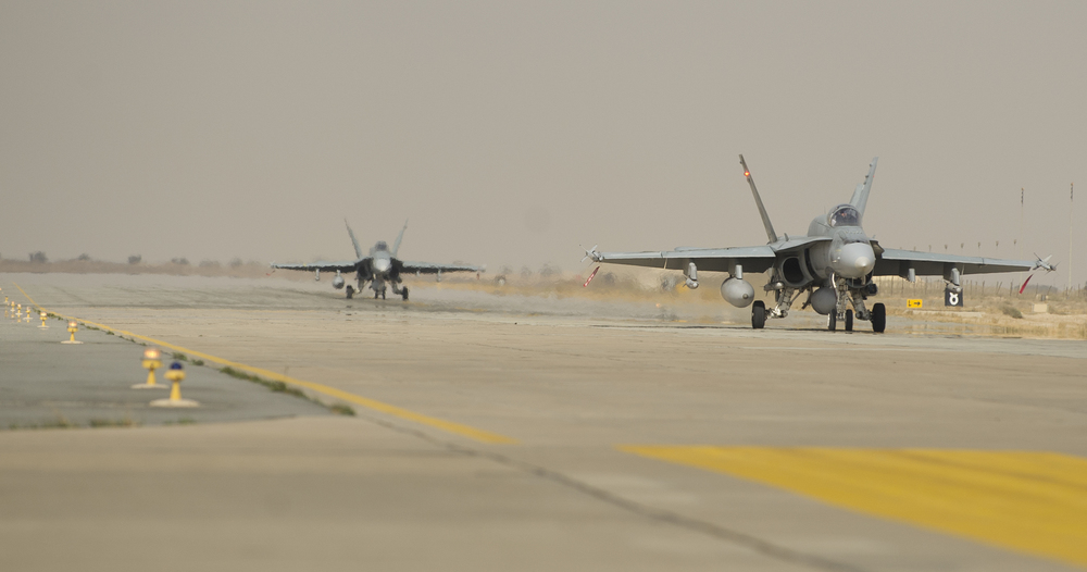 Two CF-18 Hornet fighter jets taxi out to the arm/disarm area in preparation for their next mission at Camp Patrice Vincent, Kuwait during Operation IMPACT on January 17, 2015.