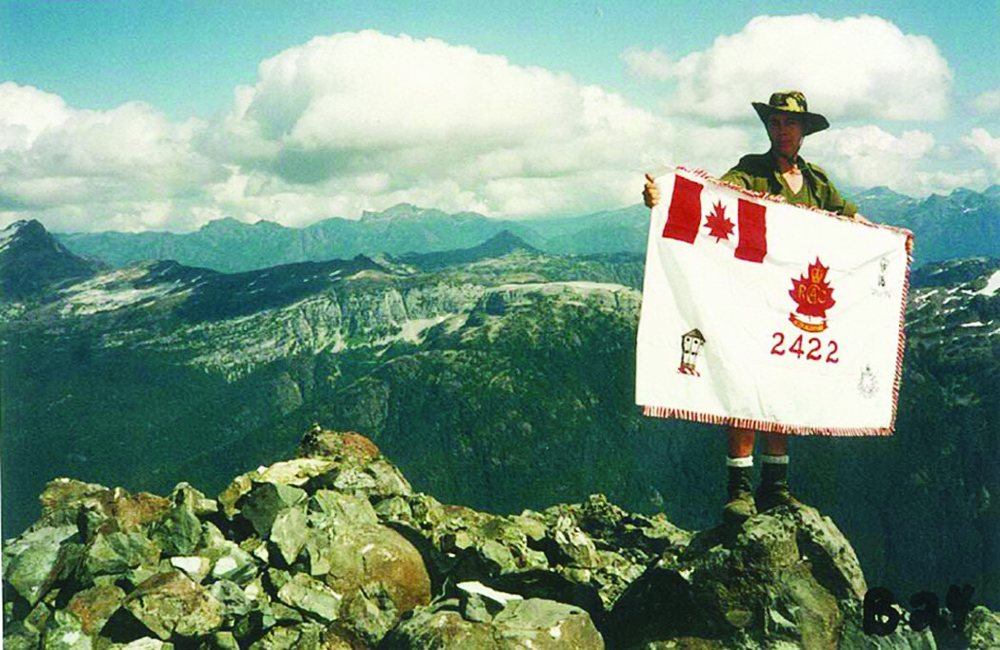 Andrew McBride holding the 2422 Royal Canadian Army Cadets banner atop the Golden Hinde, the highest peak on Vancouver Island, in September 1994.