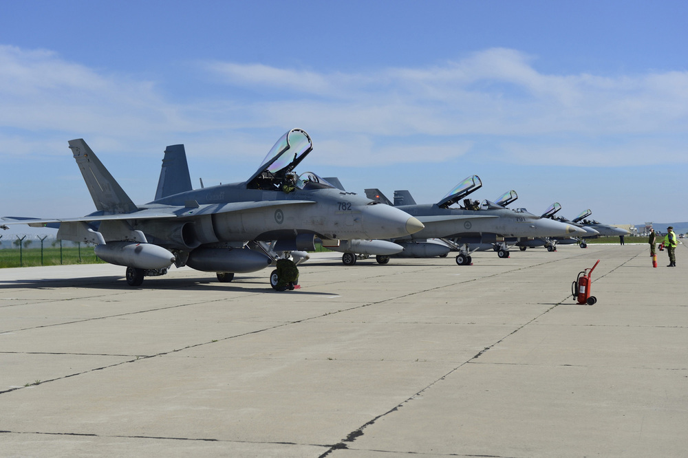 Six CF-18 fighter jets sit on an airfield. The Liberals have kept their election promise and changed the mandate of Canada's participation in the fight against Daesh and ISIS. (Combat Camera)