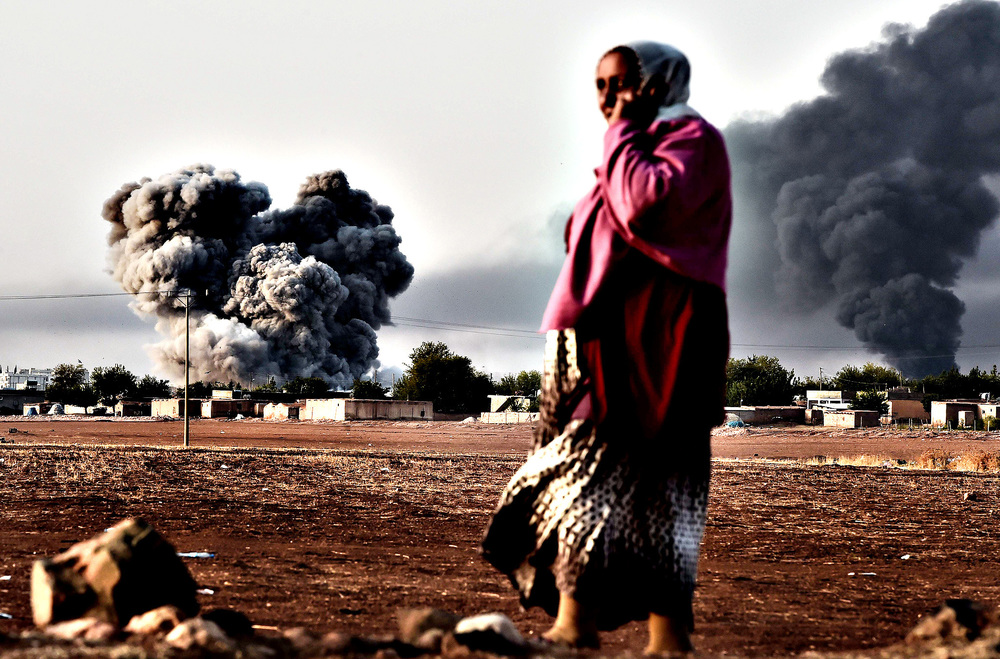 A woman speaks on a mobile phone as smoke rises after a strike from the US-led coalition on the the Syrian town of Ain al-Arab, known as Kobane by the Kurds, as seen from the Turkish-Syrian border.