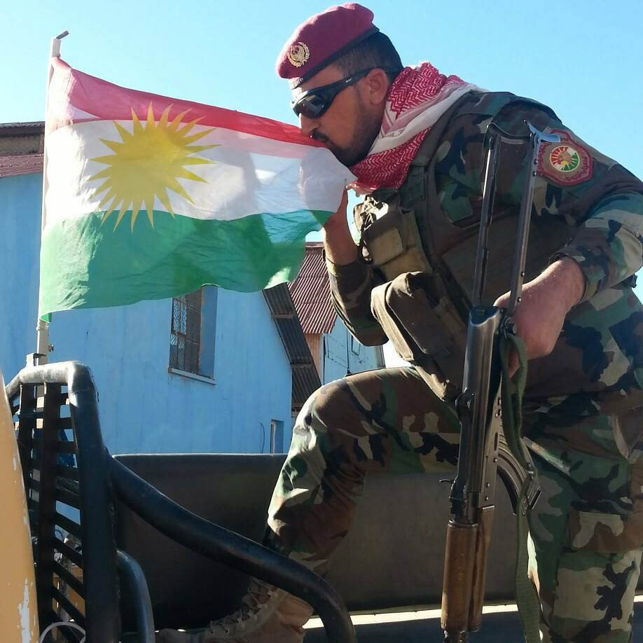 A YPG soldier affectionately kisses the flag of Kurdistan. The ultimate goal of the Kurdish Peshmerga fighting in the Middle East is to establish an independent state.