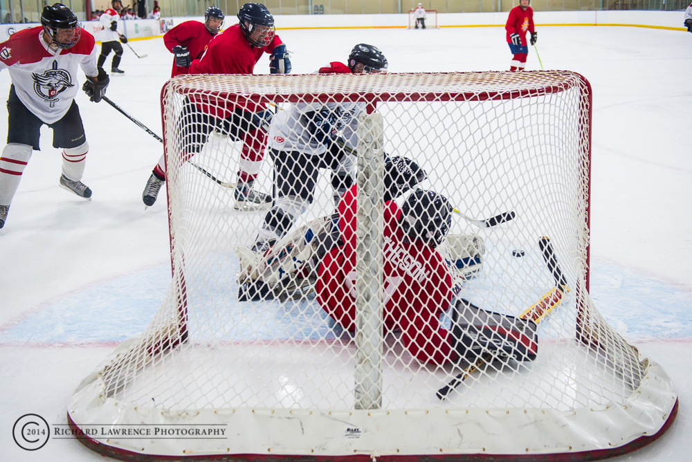Players from the Esprit de Corps Commandos hockey team go hard to the net in an attempt to sweep in a rebound during the Commando Challenge IV Charity Hockey Fundraiser in support of the MFRC - NRC.