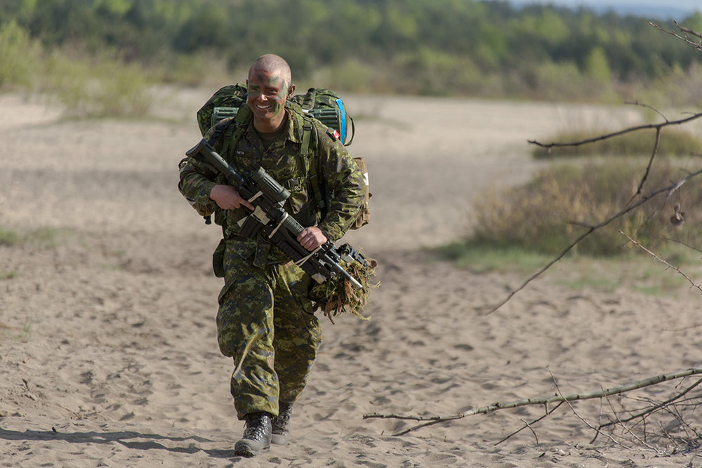 Private Cole Smith from 3rd Battalion, Princess Patricia's Canadian Light Infantry, walks to his muster point after jumping during Exercise ORZEL ALERT in the Blendowska desert region of Poland on May 5, 2014. A new initiative is now underway to make light forces a more formal part of the Canadian Army. Photo by: Jacek Szymanski Directorate Navy Public Affairs/Canadian Forces Combat Camera . ©2014 DND/MDN Canada